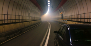 Car driving through tunnel towards light and smoke